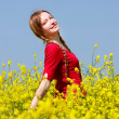 Happy girl with long hair in yellow flowers — Stock Photo
