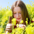 Young girl with long hair in yellow flowers - Stok fotoğraf