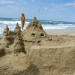 Sand castle with a girl in background — Stock Photo