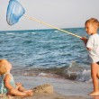 Two kids playing on beach - Stock Photo