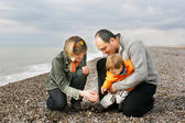 Young happy family on beach — Stock Photo