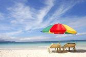 Stoelen en kleurrijke paraplu op zand strand — Stockfoto
