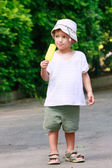 Young boy eating yellow ice-cream on natural background — Stock Photo