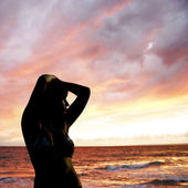Young girl silhouette on sunset sea background — Stock Photo