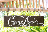 Come again phrase on wooden board — Stock Photo