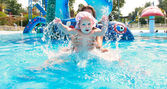 Happy baby girl with mother in waterpool — Stock Photo