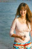 Mooi meisje met lange haren op zee achtergrond — Stockfoto