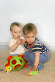 Two baby boys with toys — Stock Photo