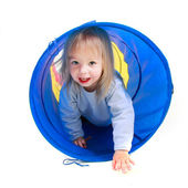 Cute toddler girl playing in colorful tube over white — Stock Photo