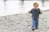 Baby boy on empty pebble beach — Stock Photo