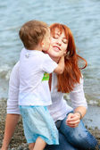 Loving mother and son on natural background — Stock Photo