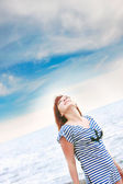 Happy girl in striped vest on sea and sky background — Stock Photo