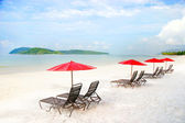 Seats and umbrellas on sand beach in tropics — Stok fotoğraf