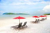 Sedadla a slunečníků na pláži s pískem v tropech — Stock fotografie