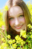Outdoor portrait of beautiful girl in yellow flowers — Stock Photo