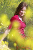 Young happy girl in yellow flower field — Stock Photo