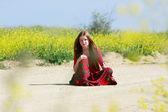 Pobre chica con el pelo largo sentado en camino rural — Foto de Stock
