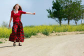Happy girl hitchhiking on country road — Stock Photo