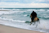 Horse rider on storm sea background — Stock Photo