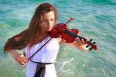 Beautifl girl playing violin on sea background — Stock Photo