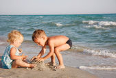 Two kids playing on beach — Stock Photo