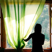 Female silhouette at open window in old hotel — Stock Photo