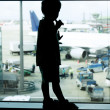 Silhouette of young boy on airport window background — Stock Photo