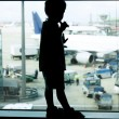Silhouette of young boy on airport window background - Stock Photo