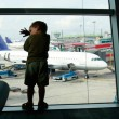 Tired boy on airport window background - Stock Photo