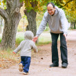 Father and son playing in autumn park - Stock Photo