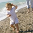 Baby going away from mother on beach — Stock Photo #12611795