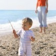 Baby and mother on pebble beach - Stock Photo