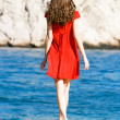 Young girl in red dress on the sea — Stock Photo