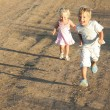 Two kids running by country road - Stock Photo