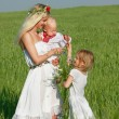 Happy mother with two children in traditional clothes outdoors - Stock Photo