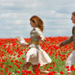 Happy couple in red poppies field — Stock Photo #12614752