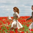 Happy couple in red poppies field — Stock Photo