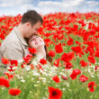 Young loving couple on red poppies field — Stock Photo #12614798