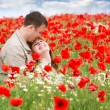 Young loving couple on red poppies field — Stock Photo