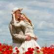 Happy couple on red poppies field — Stock Photo