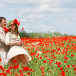 Happy couple in red poppies field — Stock Photo #12614956