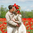 Kissing couple in red poppies field — Stock Photo