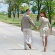 Happy couple walking by rural road - Stock Photo