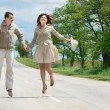 Happy couple jumping on rural road — Stock Photo