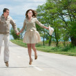 Happy couple jumping on rural road - Stock Photo