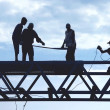 Silhouette workers on construction site - Stock Photo