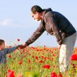 Father giving poppy flower to his son — Stock Photo