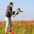 Father and son playing on poppy field — Stock Photo #12615072