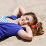 Young beautiful woman laying on sand beach — Stock Photo #12615216