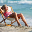Stock Photo: Young girl relaxing on sebackground